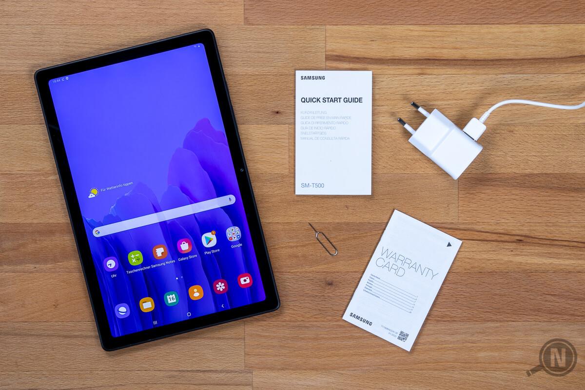 Links eingeschaltetets Samsung Galaxy Tab A7, rechts davon Quick Start Guid, SIM-Tool, Warranty-Card und Netzteil