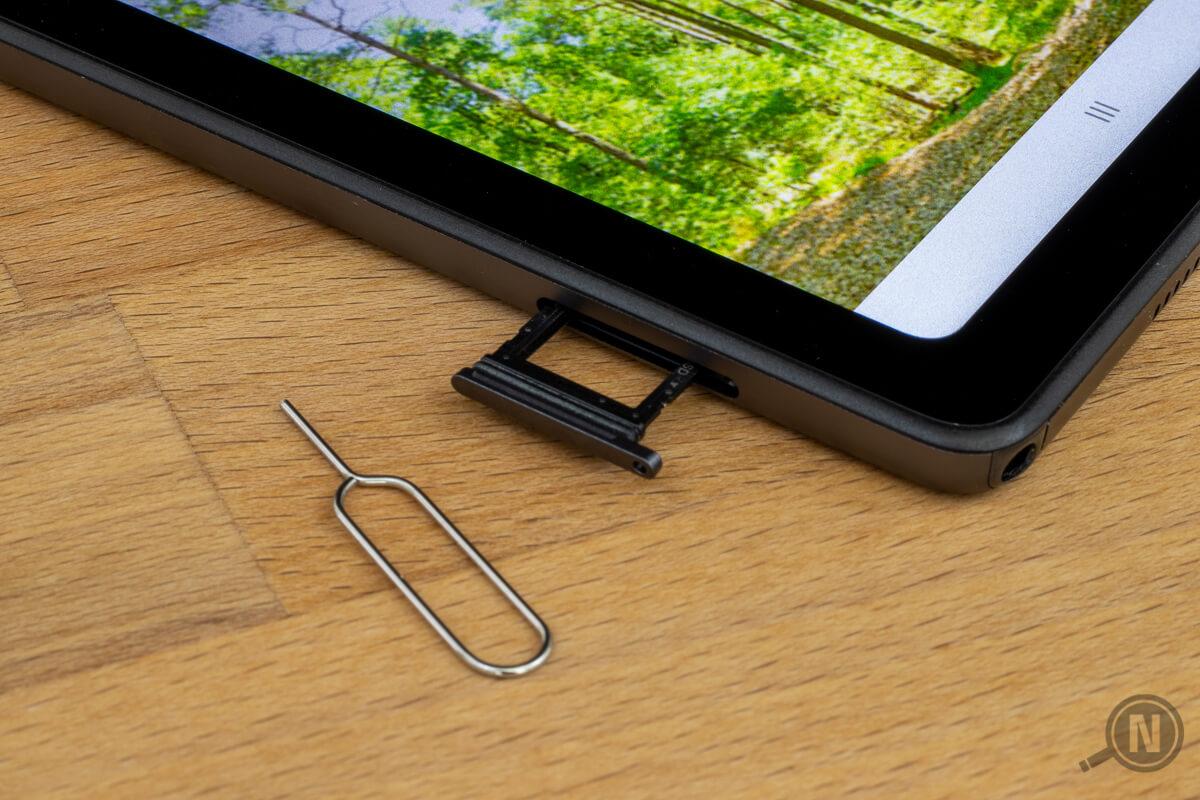 Ecke eines Tablets mit herausgezogenem SIM-Slot, daneben ein kleines Werkzeug zum Öffnen des Einschubs aus gebogenem Draht