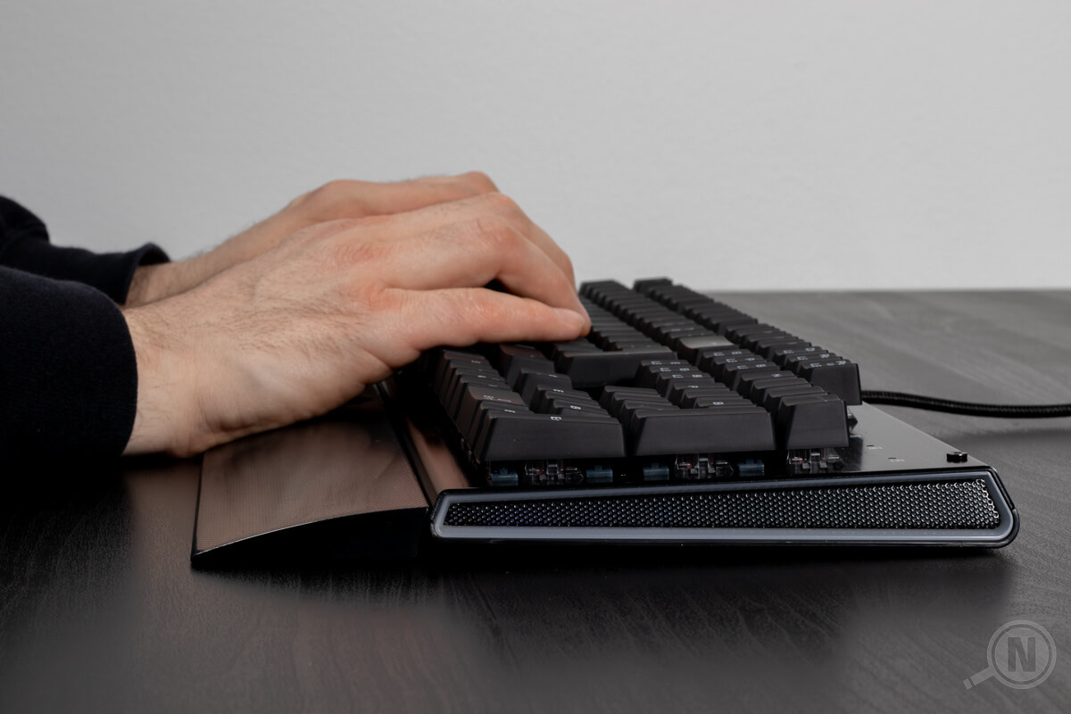 Gaming-Tastatur mit Handballenauflage und tippenden Haenden.
