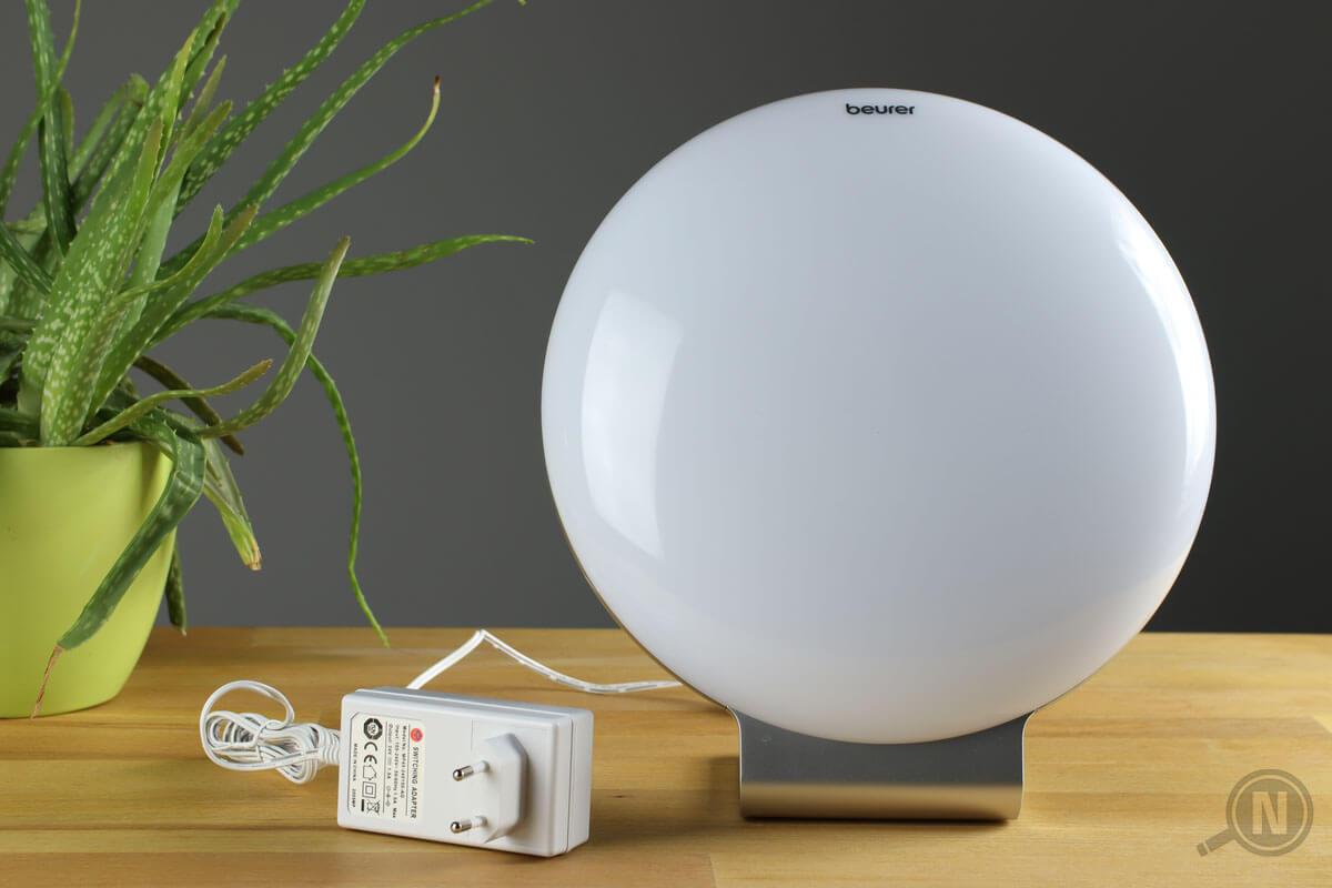 Eine Tageslichtlampe mit Netzteil liegt auf einem Holztisch. Am linken Bildrand befindet sich eine Topfpflanze.