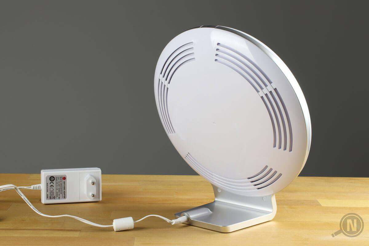 Die Rückseite einer auf einem Tisch stehenden Tageslichtlampe; das Netzteil liegt links daneben.