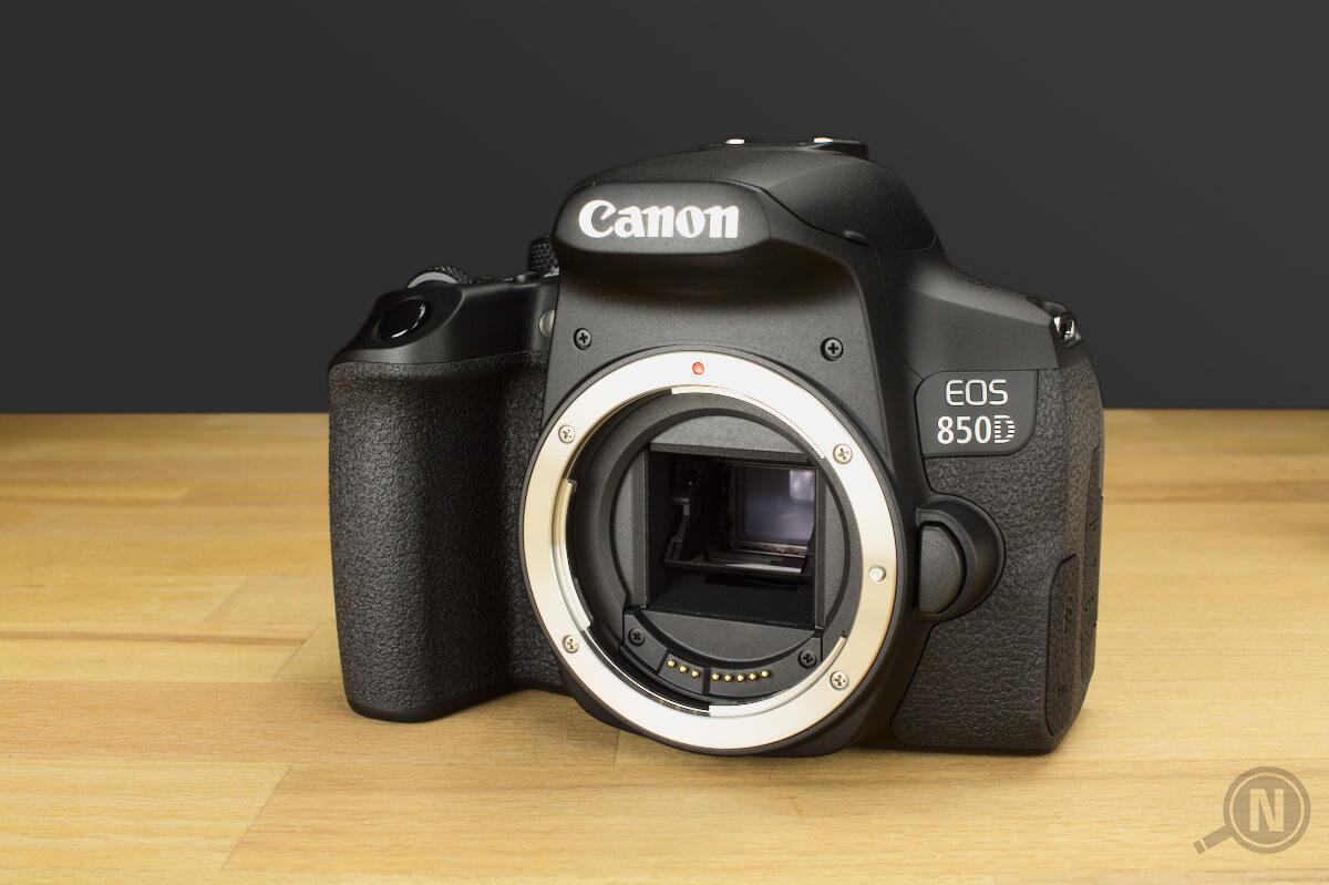 Eine Spiegelreflexkamera mit abgenommenem Objektiv auf einer hölzernen Tischplatte.