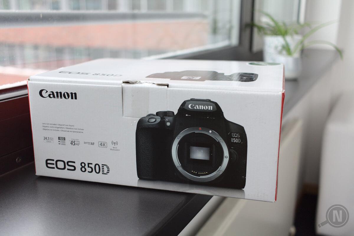 Kartonverpackung einer Kamera auf einem Fensterbrett, verschwommene Zimmerpflanzen im Hintergrund