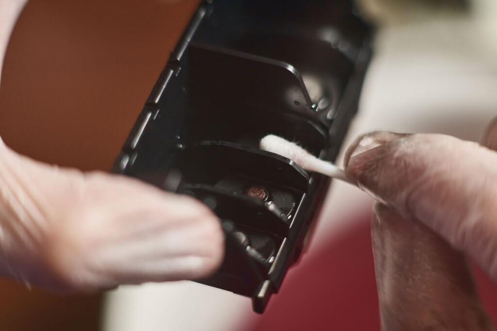 Person reinigt Druckkopf mit Wattestaebchen