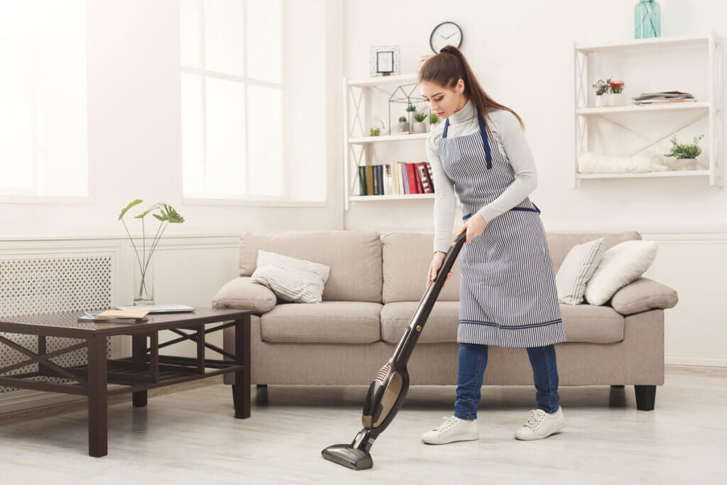 Akku-Staubsauger Frau saugt in Wohnzimmer