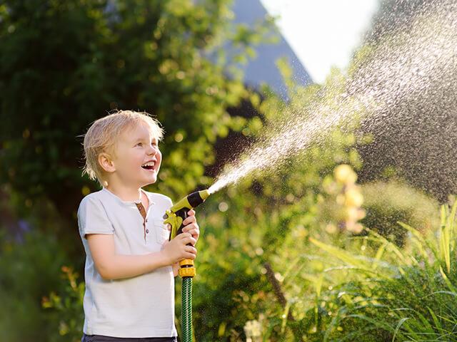 Kind mit Wasserschlauch