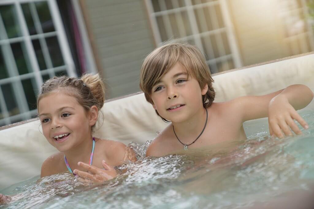 zwei kinder sitzen im aufblasbaren whirlpool