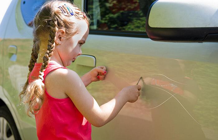 Kind zerkratzt Auto