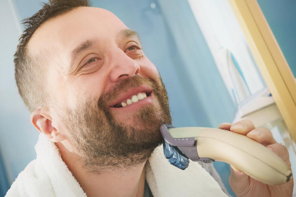 Barttrimmer Mann beim Bart trimmen