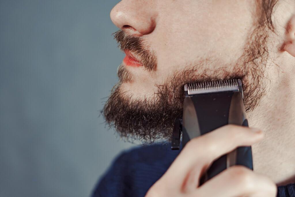 Barttrimmer Mann trimmt sich Bart