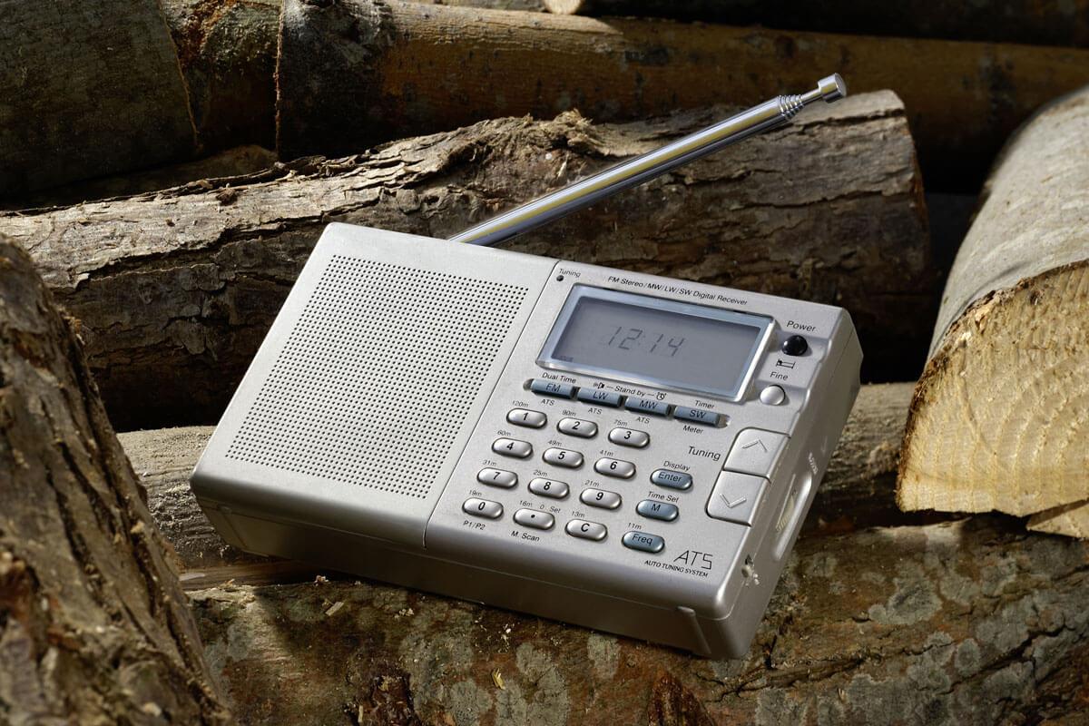 baustellenradio liegt auf holzstaemmen