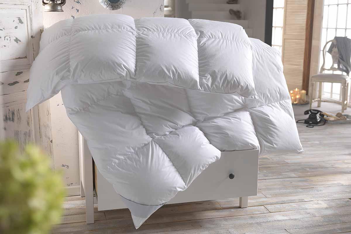 dicke Bettdecke wird in einem laendlichen Wohnzimmer gelueftet