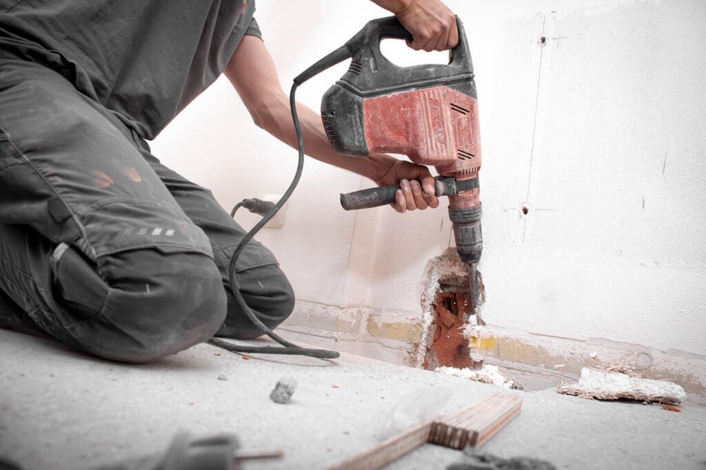 Installateur stemmt Loch mit Bohrhammer in die Wand.