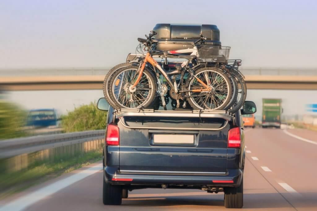 Ein mit Dachbox und Fahrraedern beladenes Auto fährt auf der Autobahn.