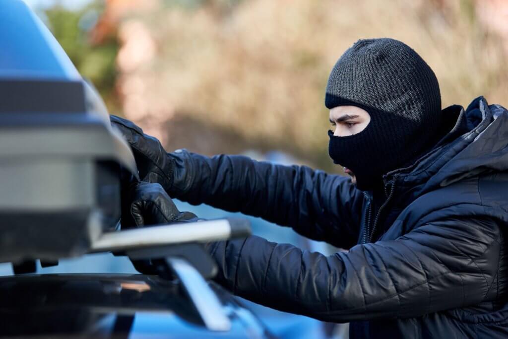 Ein maskierter Mann versucht, eine Dachbox aufzubrechen.