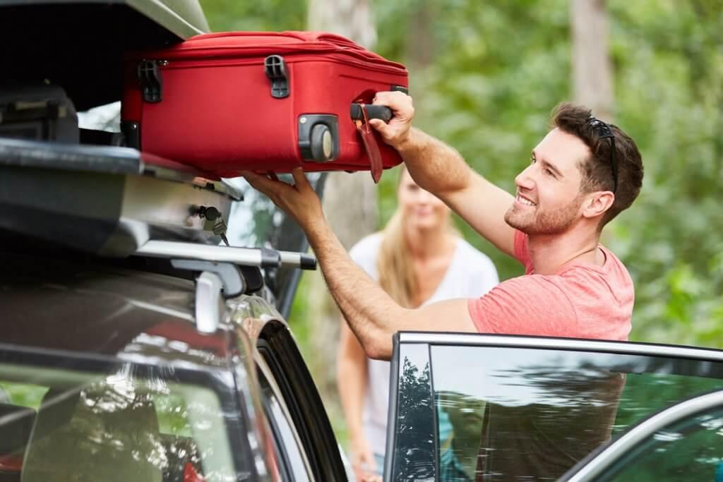 Ein Mann legt einen roten Koffer in eine Dachbox.
