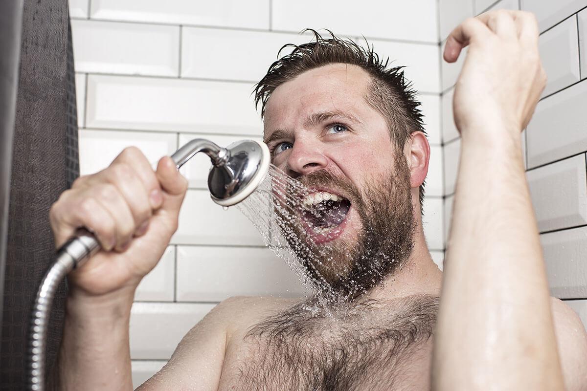 Mann singt in Dusche und nutzt Duschkopf als Mikrofon