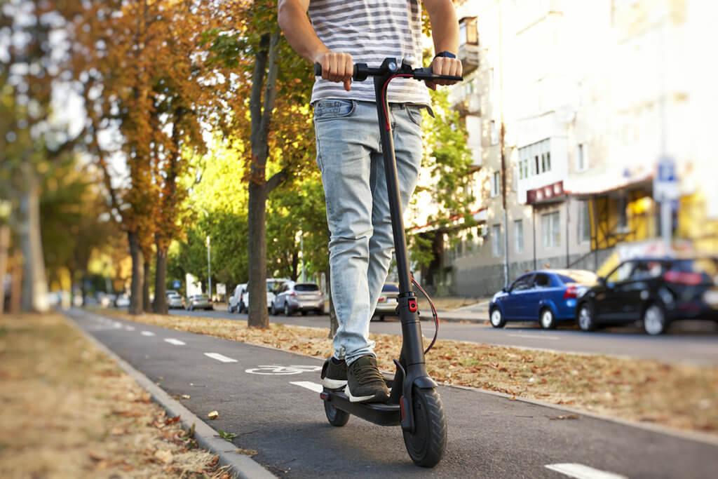 Mann auf Elektro-Scooter faehrt durch Stadt