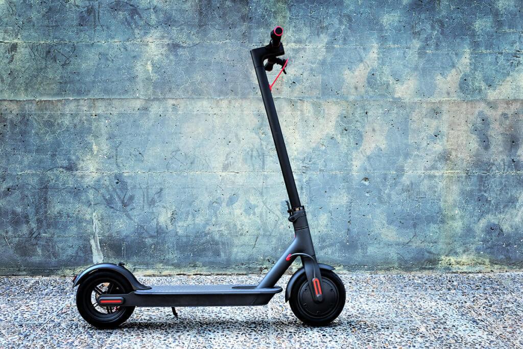 Elektro-Scooter vor einer blaeulichen Wand