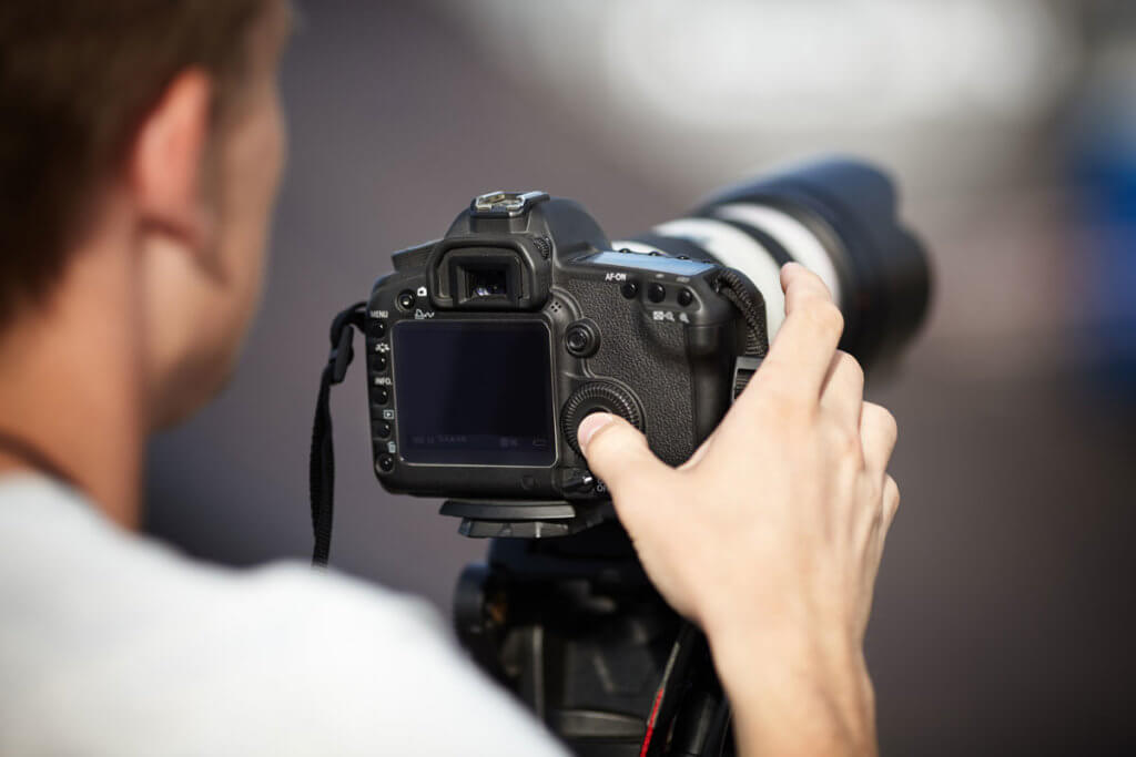 Mann stellt seine Kamera mit Teleobjektiv ein.