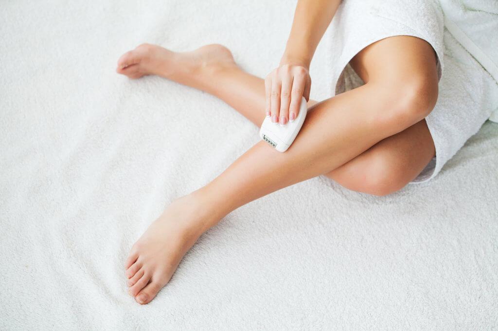 Frau epiliert sich Beine