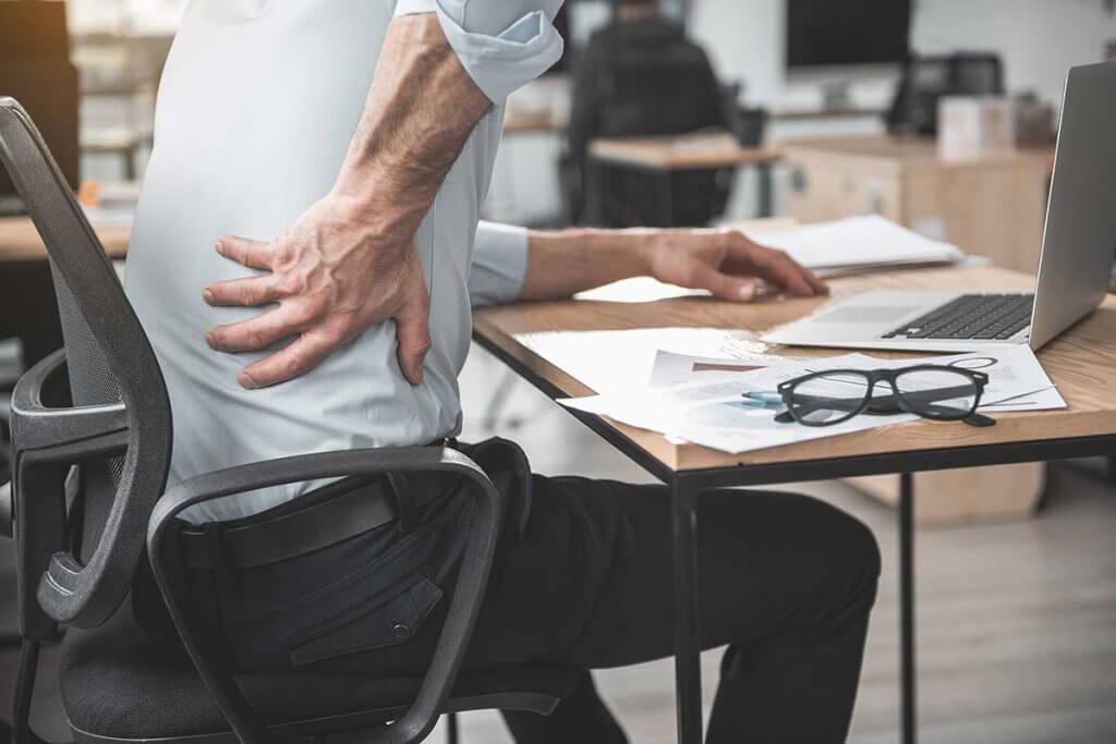 person hat rueckenschmerzen am arbeitsplatz