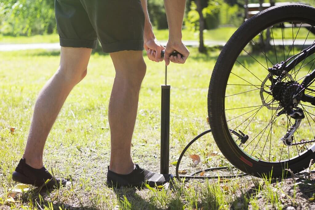 Mann pumpt Fahrradreifen