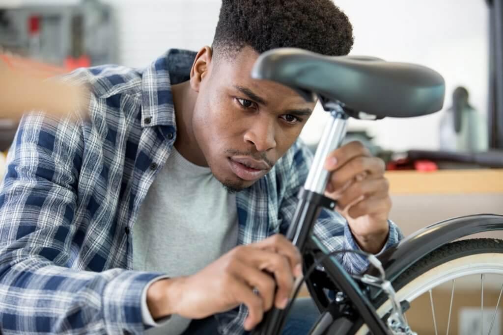 Mann inspiziert Sattelrohr seines Rades