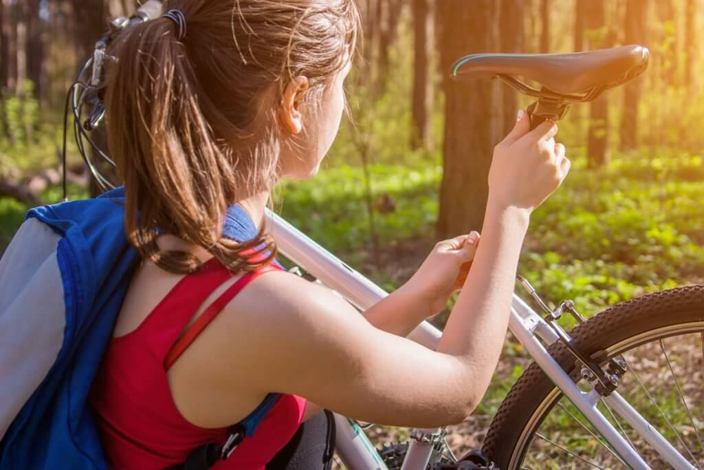 Junge Frau stellt ihren Fahrradsattel im Wald ein