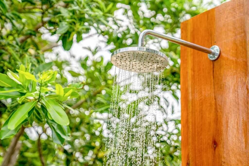 Nahaufnahme des Duschkopfs einer Gartendusche, aus dem Wasser kommt