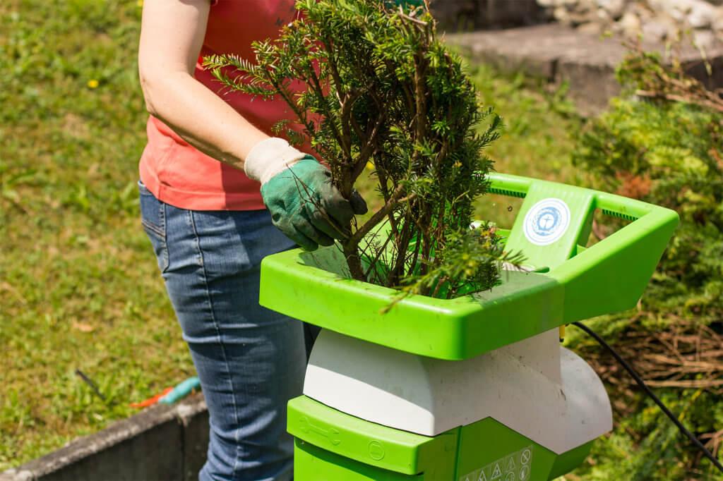 Frau macht Gartenarbeit mit Haecksler