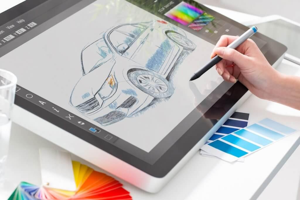 grafiktablett mit display, hand haelt stift. auf dem bildschirm ist eine zeichnung von einem auto.
