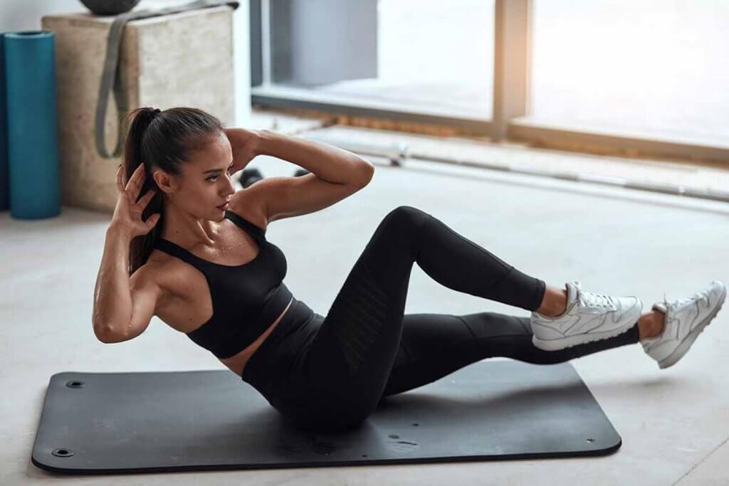 sportliche frau trainert auf einer fitnessmatte