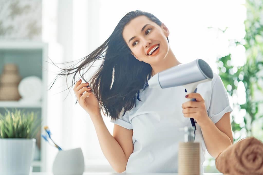 Frau föhnt sich Haare im Bad