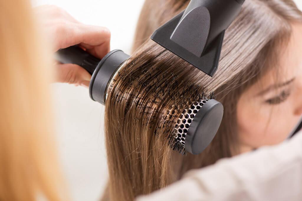Frau trocknet sich die Haare