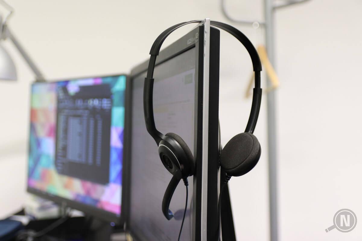 Seitlicher Blick auf Bildschirm, an dem ein Headset hängt