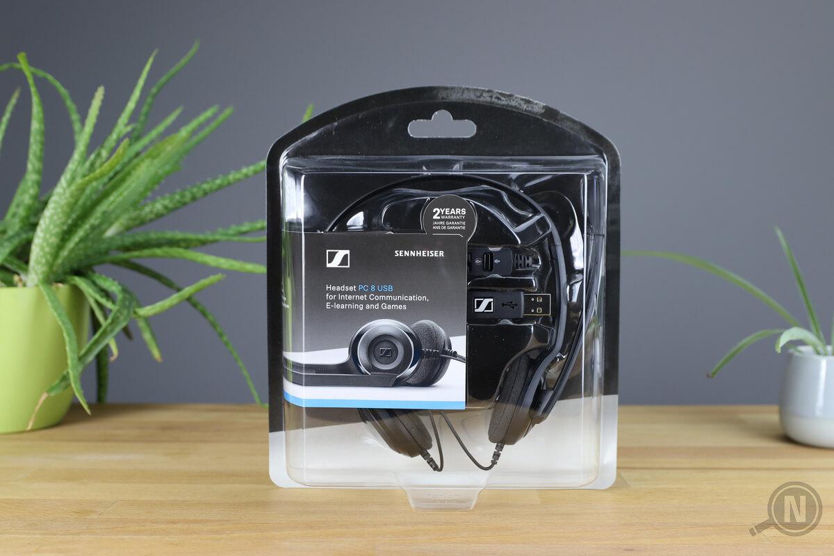 Headset von Sennheiser in transparenter Kunststoffverpackung zwischen zwei Pflanzen auf Holztisch