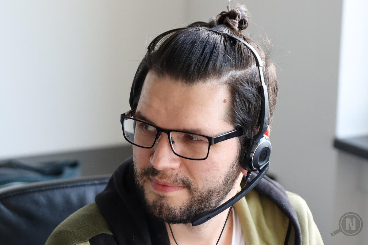 Halbprofil eines jungen Mannes mit Dreitagebart, Brille und am Hinterkopf zusammengeknoteten Haaren, der ein Headset trägt