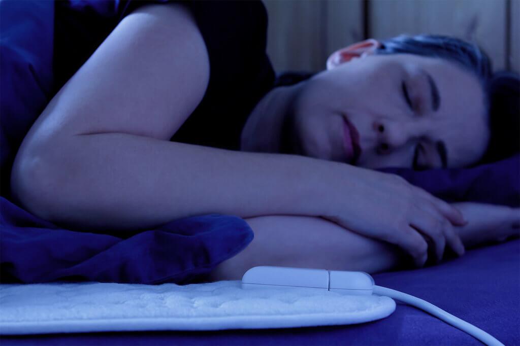 Frau schläft auf Heizdecke