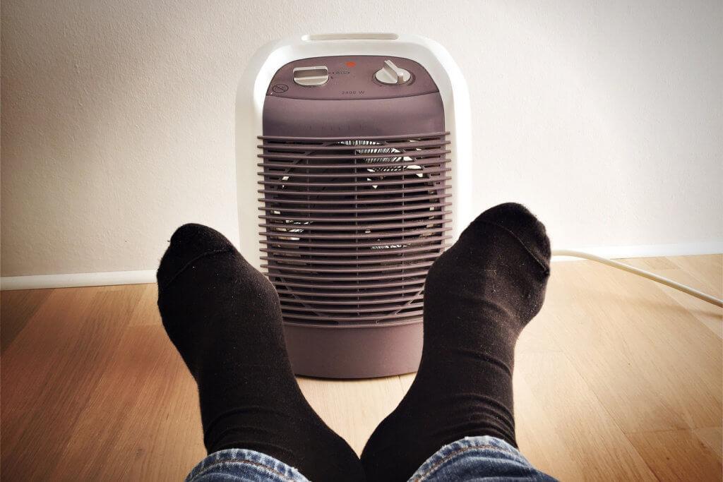 Füße vor Heizlüfter wärmen