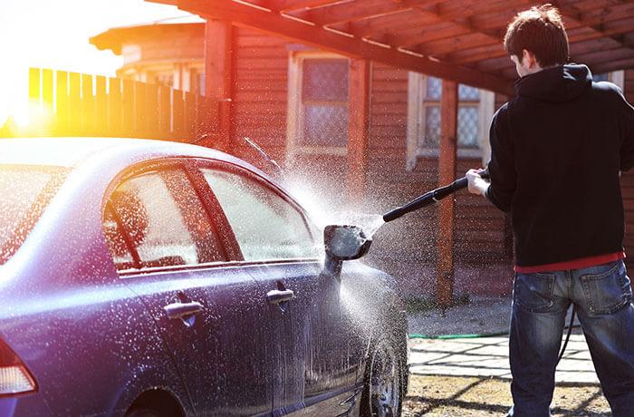 Mann wäscht Auto mit Hochdruckreingier