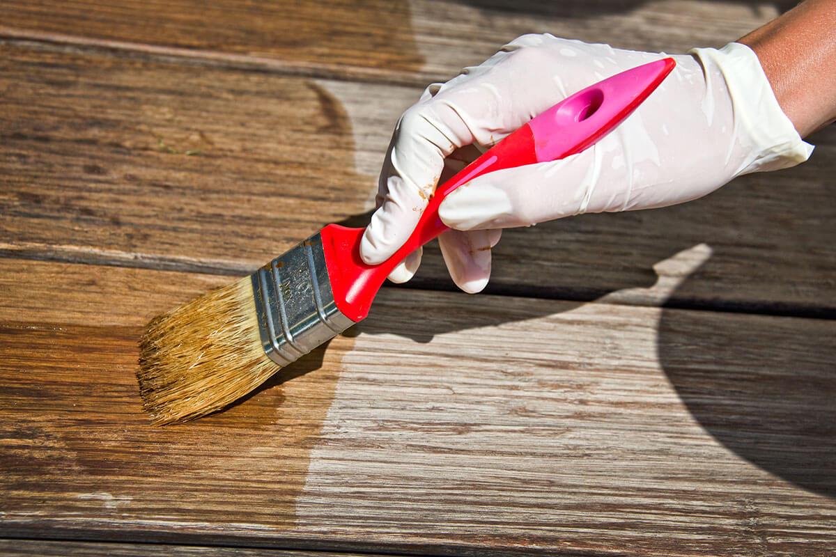 Person tragt beim Streichen von Holzlasur Handschuhe