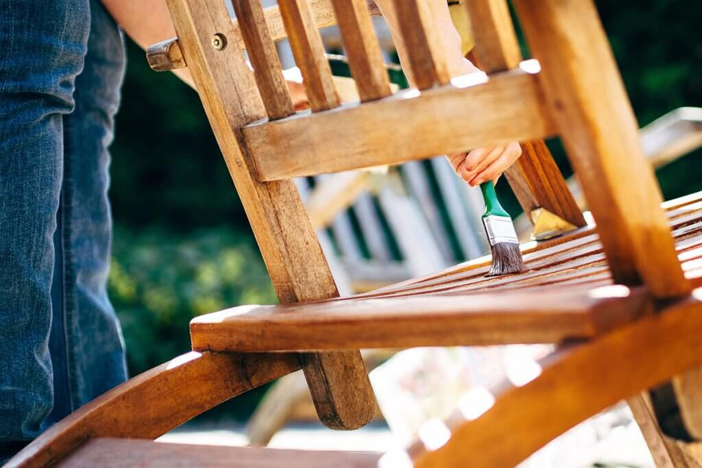 Holzmoebel auf Terrasse werden lasiert