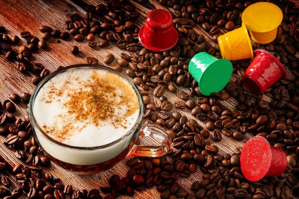 kaffeekapselmaschine tasse cappuccino mit kapsel und kaffeebohnen