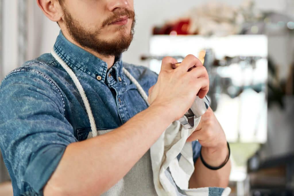 Mann reinigt eine Kaffeemuehle