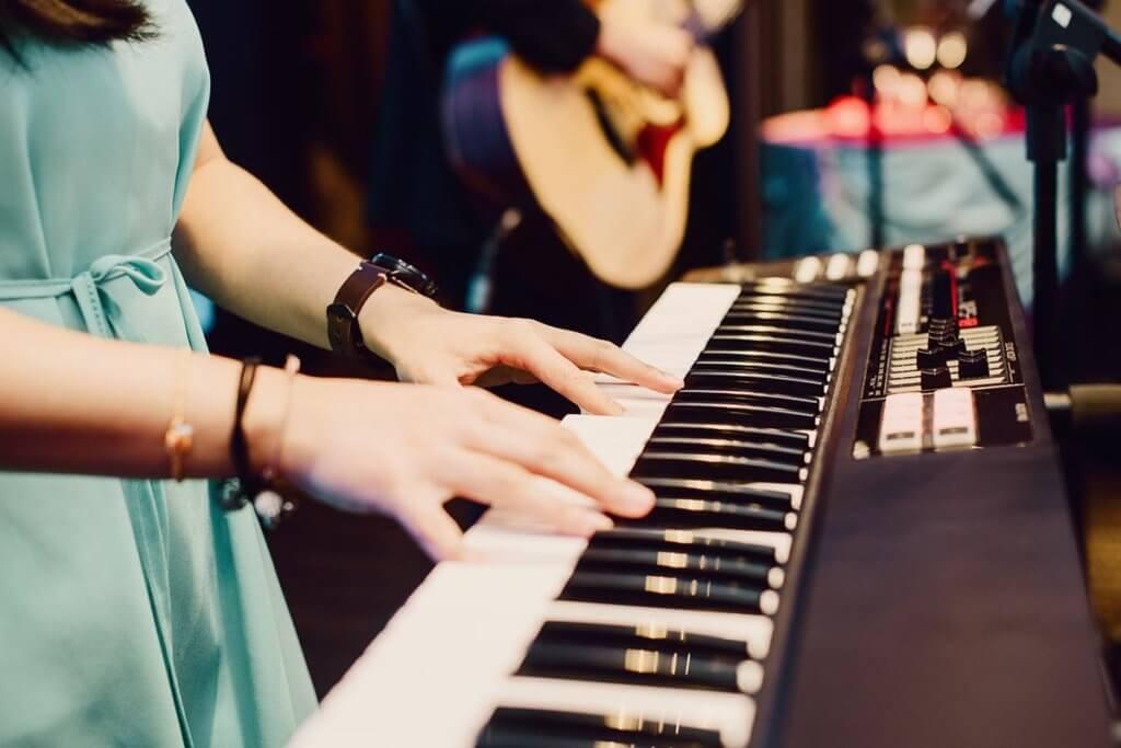 Frau am keyboard im Proberaum der Band