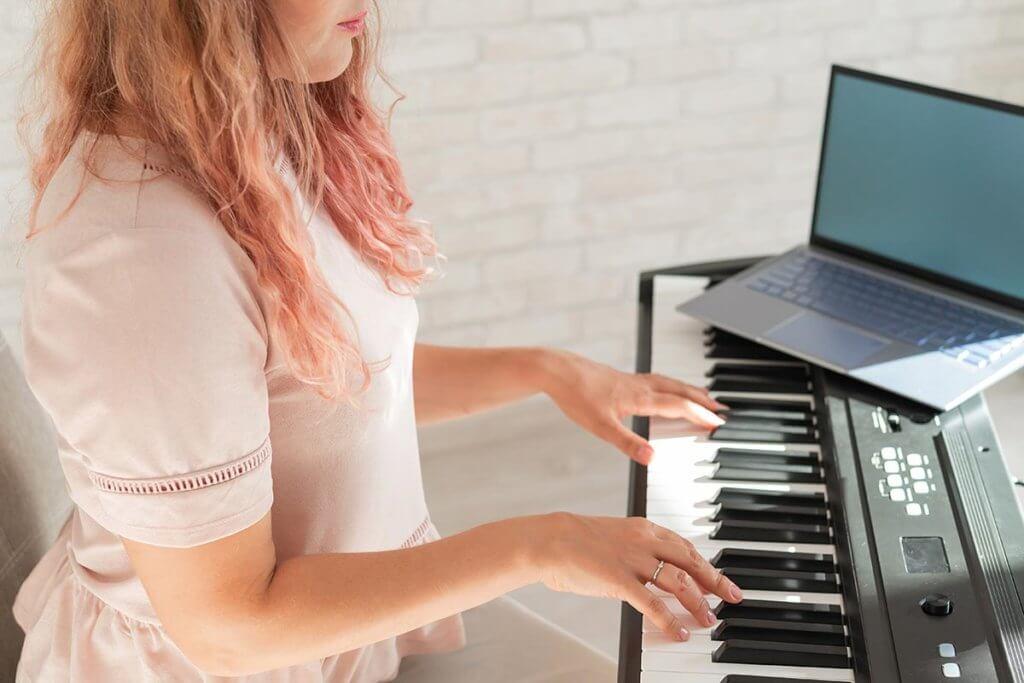 Frau am Keyboard mit Laptop