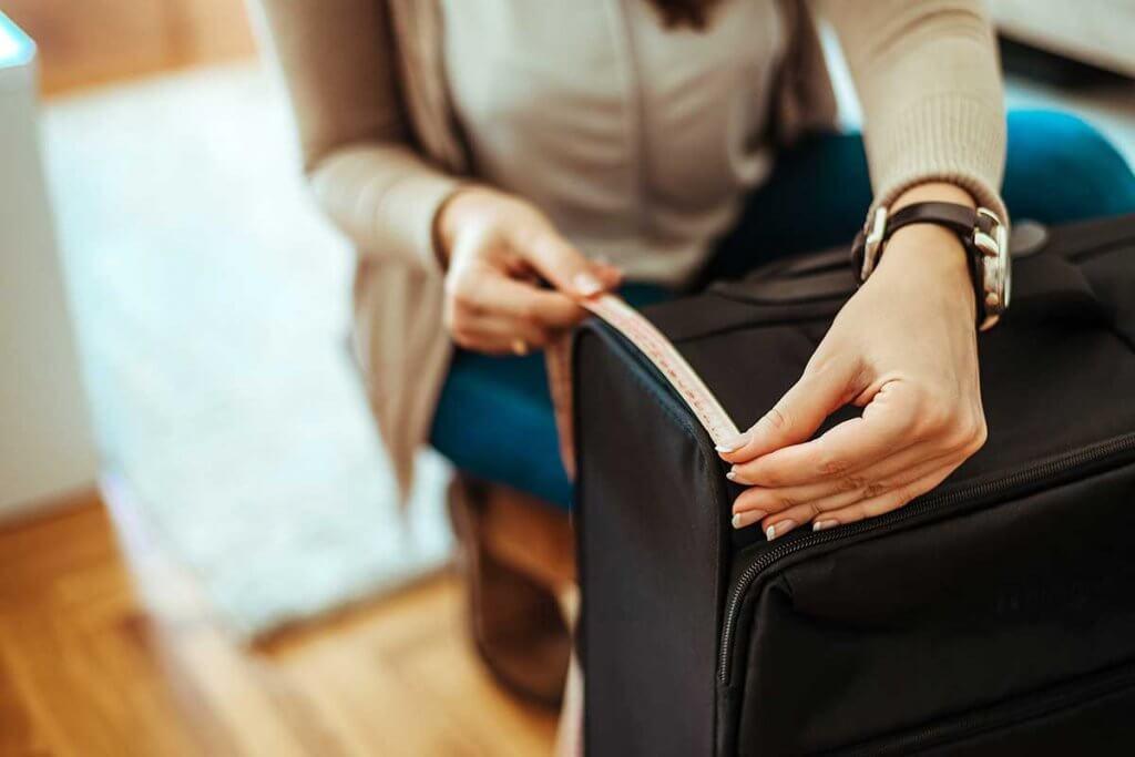 Frau misst Kofferabmessungen