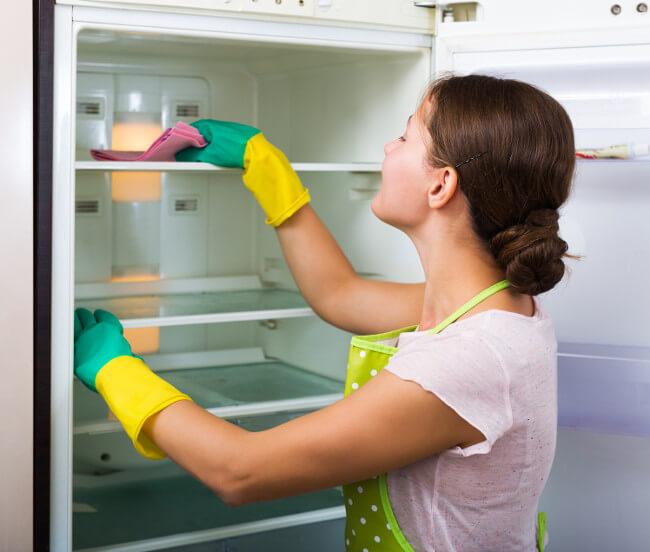 Frau reinigt Kühlschrank