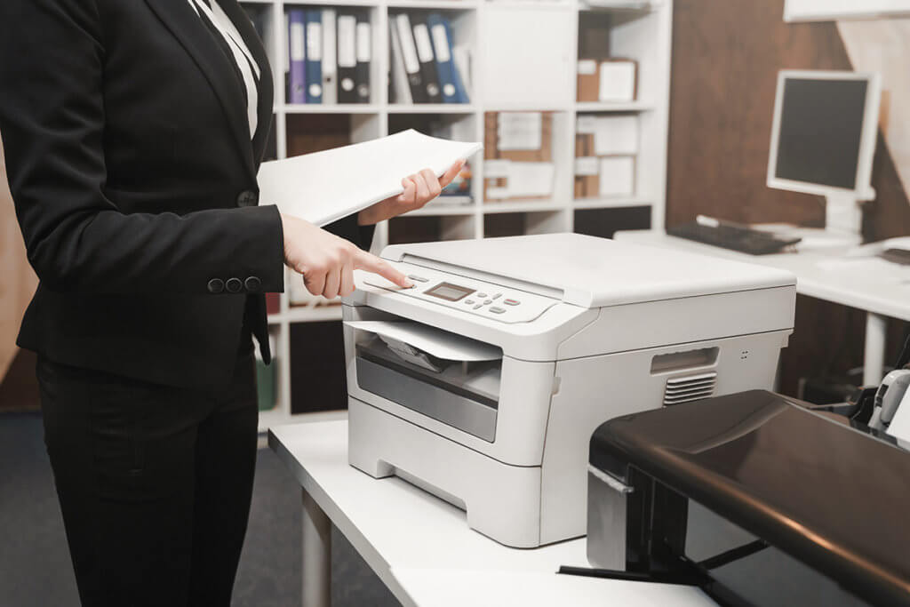 Frau in Blazer nutzt Multifunktionsdrucker in einem Buero